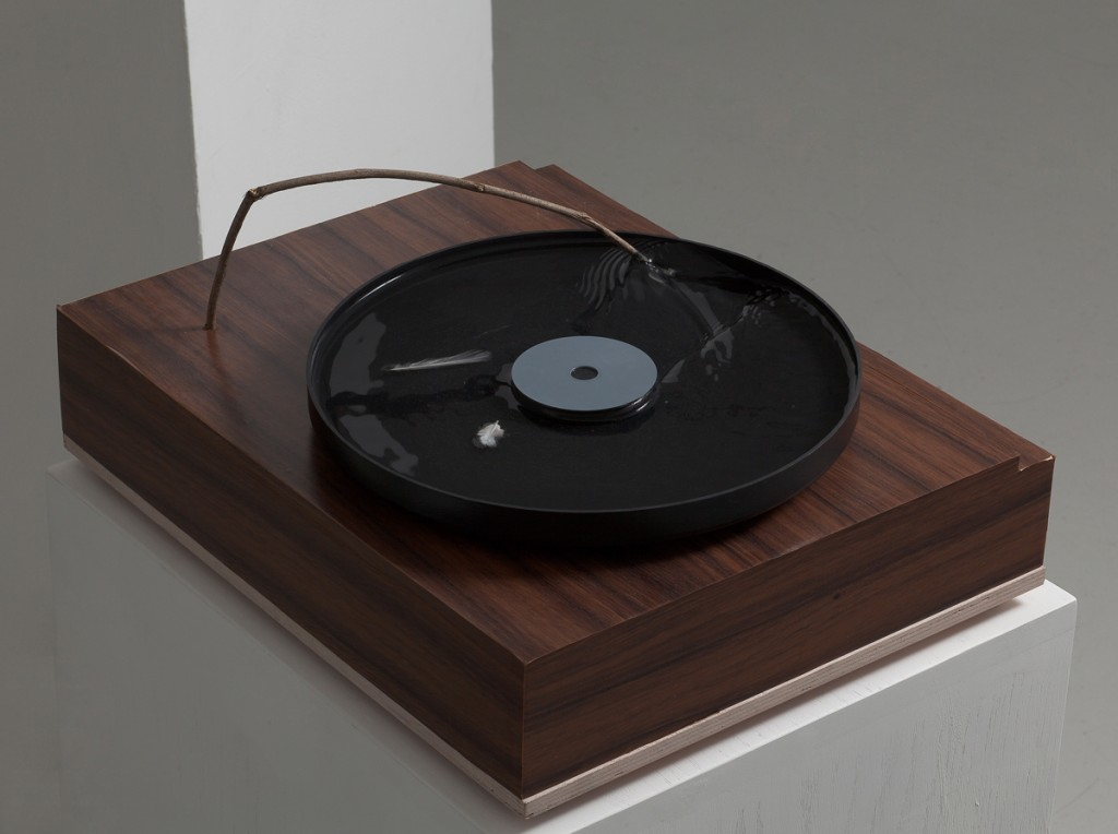 Talia Keinan, Record Player, Wooden panel, rubber, water, twig and feathers, 46x37x20cm, 2010