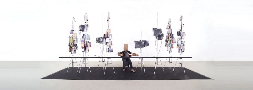 Chanan De Lange, Instrument Man Installation, Mirror, aluminum rods, television monitors, books, obelisk chair, light bulbs, black paint, brassier shoulder straps, 250x150x600cm, 2005